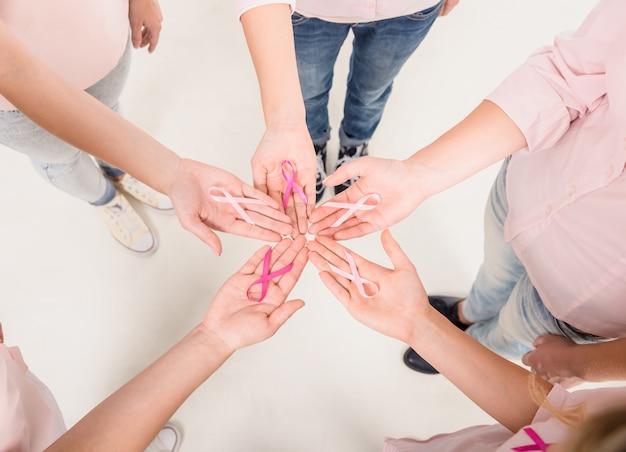 Femmes heureuses en cercle avec des rubans roses pour le cancer du sein. Photo Premium