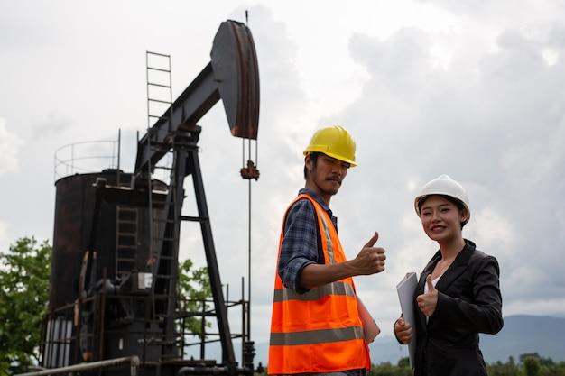 Les femmes ingénieurs consultent des ouvriers à côté de pompes à huile fonctionnant avec un ciel Photo gratuit