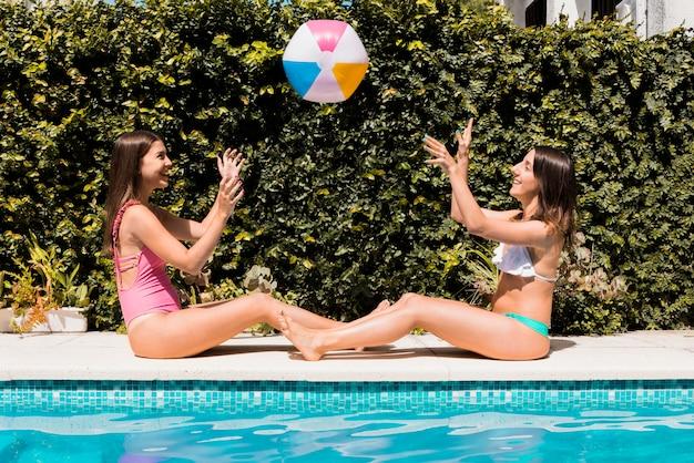 Femmes jouant avec une balle de caoutchouc près de la piscine Photo gratuit