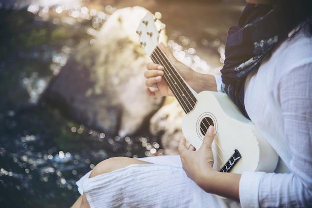 Les femmes jouent ukulélé nouveau à la cascade Photo gratuit
