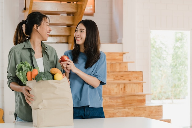 Femmes lesbiennes lgbtq asiatiques détiennent des sacs en papier d'épicerie à la maison Photo gratuit