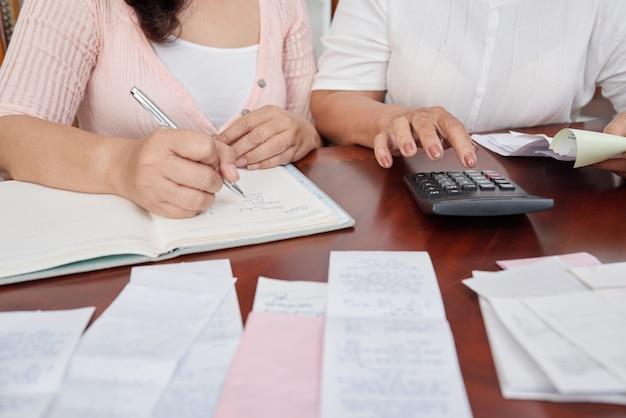 Femmes méconnaissables assises à la table avec des reçus, comptant sur une calculatrice et écrivant dans un journal Photo gratuit
