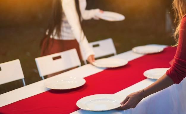 Les femmes mettent la table pour le dîner Photo gratuit