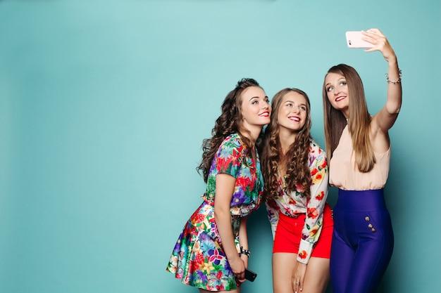 Femmes à la mode en vêtements faisant photo au téléphone intelligent. Photo Premium