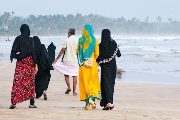 Les femmes musulmanes marchent le long de la plage, un homme marche en avant. Photo Premium