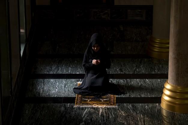 Les femmes musulmanes portant des chemises noires font la prière selon les principes de l'islam. Photo Premium