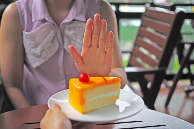 Les femmes perdent du poids. choisissez de ne pas obtenir une assiette de gâteau que des amis envoient. Photo Premium