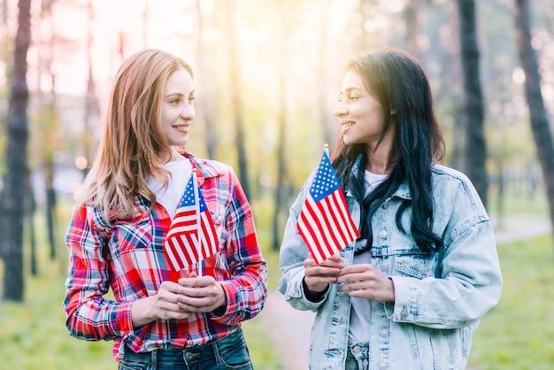 Femmes avec petits drapeaux américains debout à l'extérieur Photo gratuit