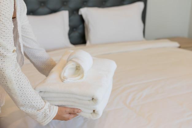 Les femmes placent de petites serviettes et des serviettes blanches. sur le lit d'hôtel. Photo Premium
