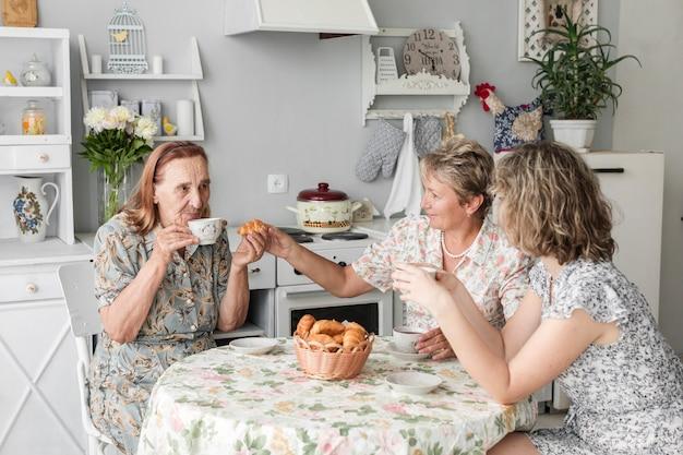Femmes de plusieurs générations dégustant un croissant avec du café au petit-déjeuner Photo gratuit