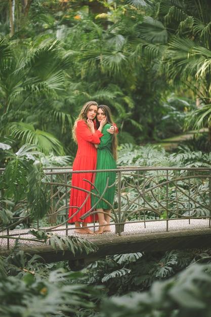 Femmes sur un pont entouré de feuillage Photo gratuit