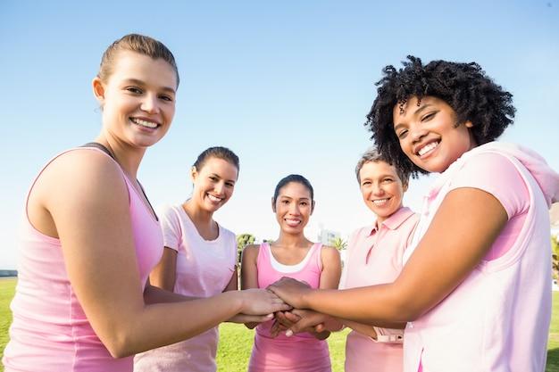 Des femmes portant du rose pour le cancer du sein et se serrant les mains Photo Premium