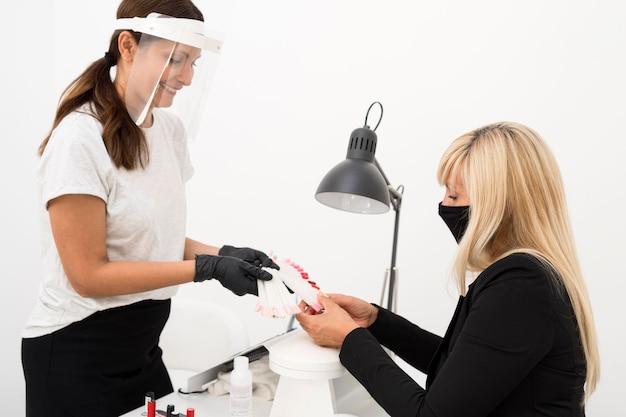 Femmes Portant Un Masque Et Un Bouclier Au Salon De Manucure Photo gratuit