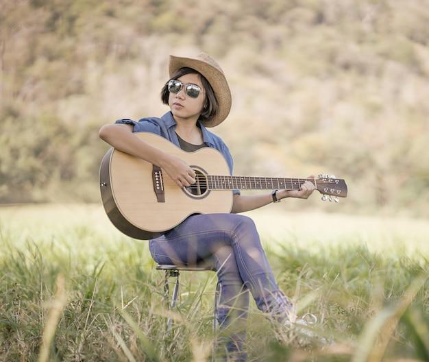 Les femmes portent un chapeau et des lunettes de soleil pour jouer de la guitare dans l'herbe Photo Premium