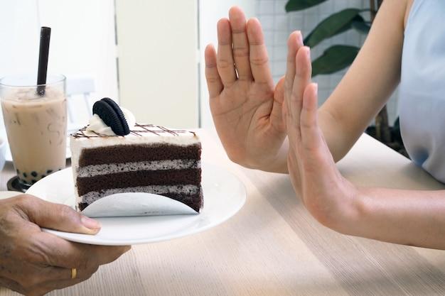 Les femmes poussent l'assiette à gâteau et le thé au lait perlé. arrêtez de manger un dessert pour perdre du poids. Photo Premium