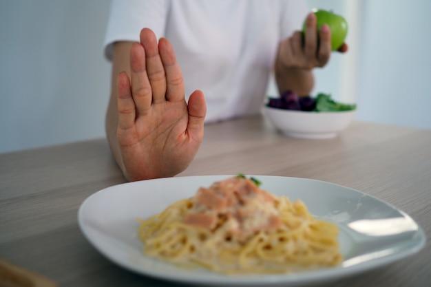 Les femmes poussent des plats qui sont supposés être un mélange de gras trans. Photo Premium