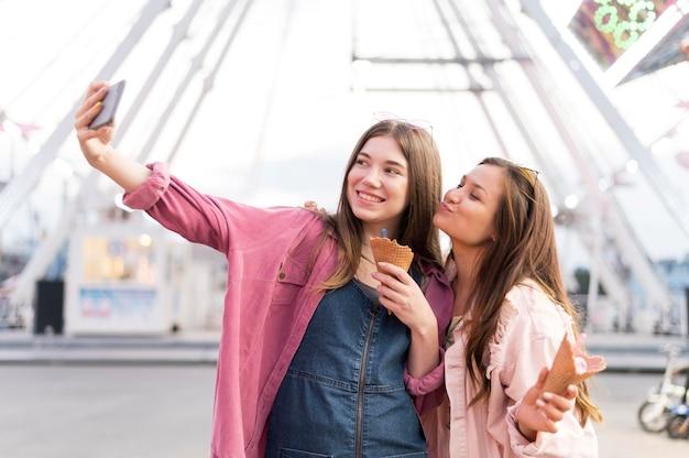 Femmes Prenant Selfie Ensemble Au Parc D'attractions Photo gratuit