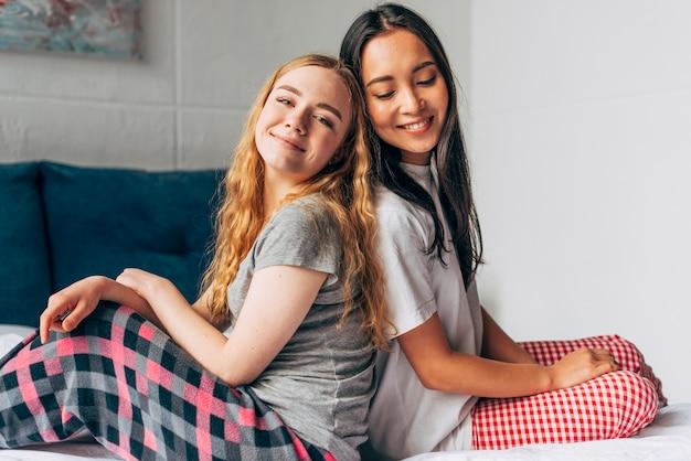 Femmes en pyjama assis sur un lit Photo gratuit