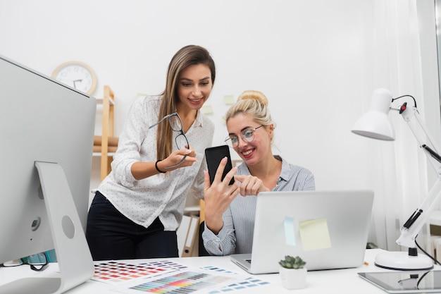 Femmes à la recherche au téléphone au bureau Photo gratuit