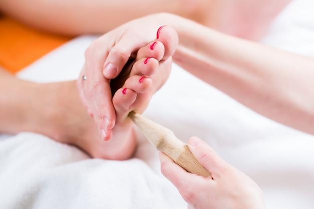Femmes en réflexologie ayant le pied massé Photo Premium