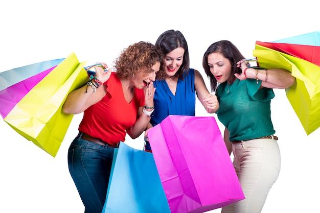 Les femmes regardant les courses à l'intérieur des sacs et se surprenant sur un fond blanc. Photo Premium