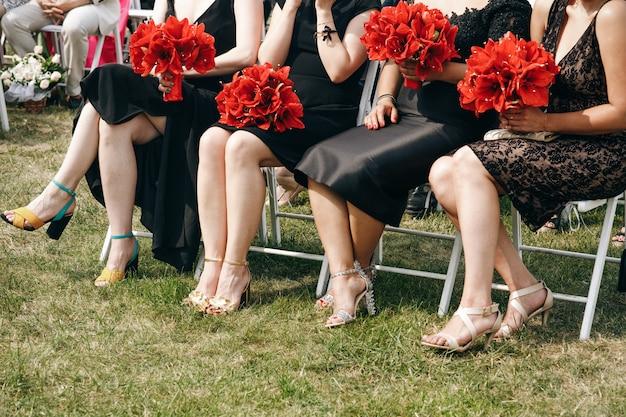 Les femmes en robe noire tiennent le bouquet de lis rouges Photo gratuit