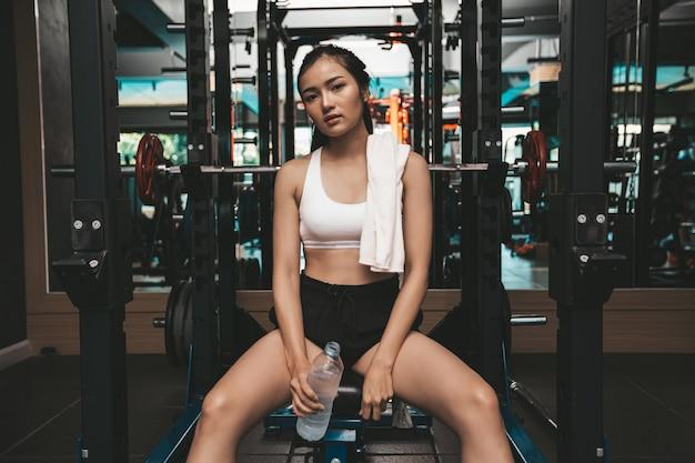 Les femmes s'assoient et se détendent après l'exercice. tenir une bouteille d'eau et un chiffon blanc sur le cou. Photo gratuit