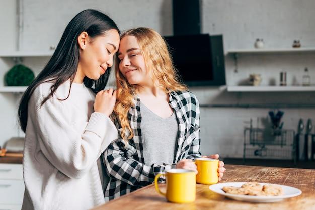 Les femmes à la table embrassant Photo gratuit