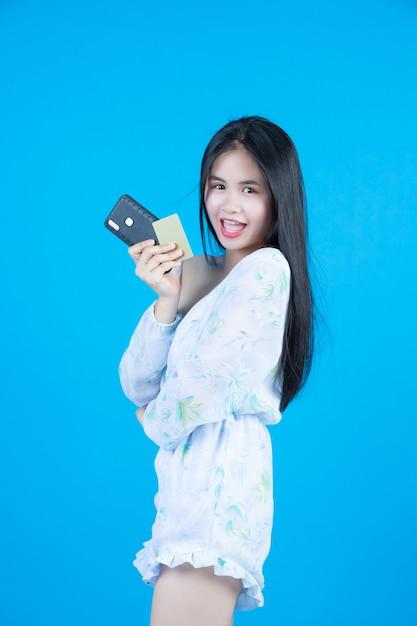 Femmes tenant des cartes à puce et des téléphones portables gris Photo gratuit