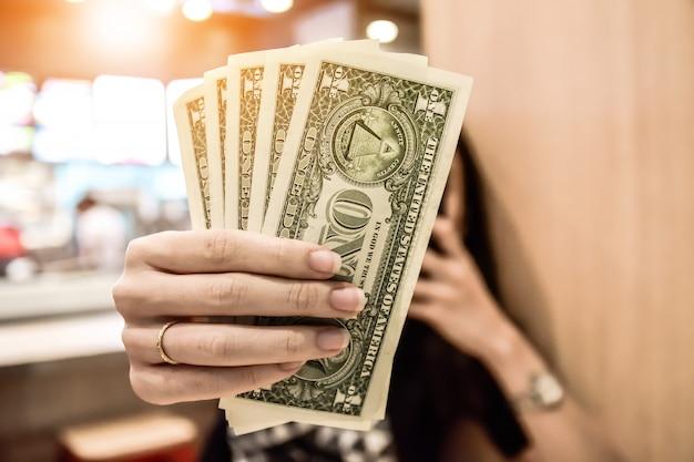 Femmes tenant un dollar sous la main Photo Premium