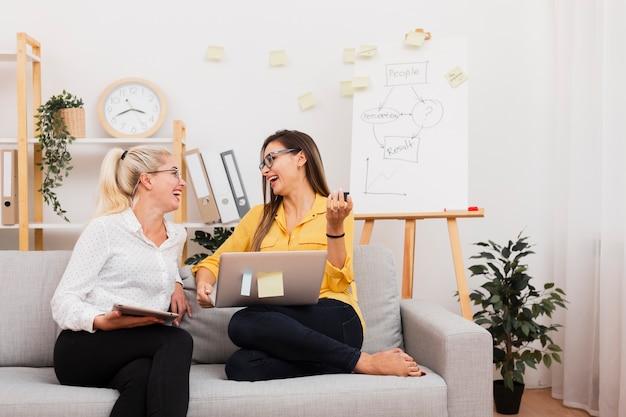 Femmes tenant des gadgets et assis sur un canapé Photo gratuit