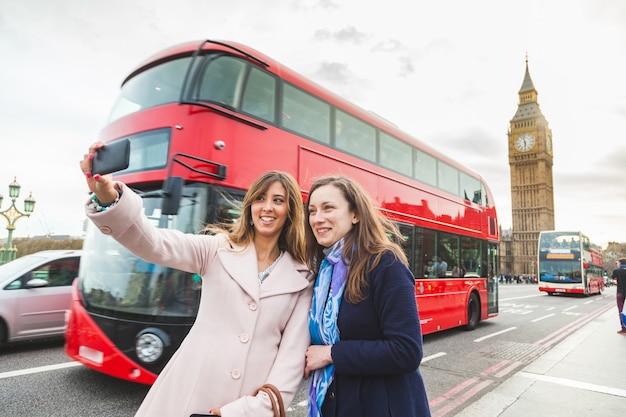 Femmes touristes prenant un selfie à big ben à londres Photo Premium