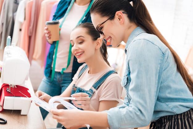 Femmes à l'usine de vêtement l'une d'elles montrant un plan Photo Premium