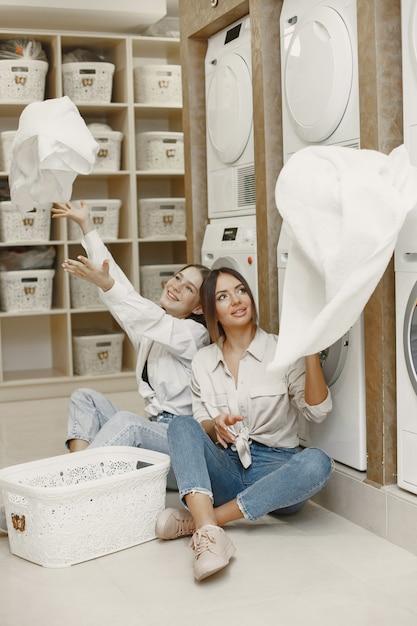 Les Femmes Utilisant Une Machine à Laver Font La Lessive. Jeunes Filles Prêtes à Laver Les Vêtements. Intérieur, Concept De Processus De Lavage Photo gratuit