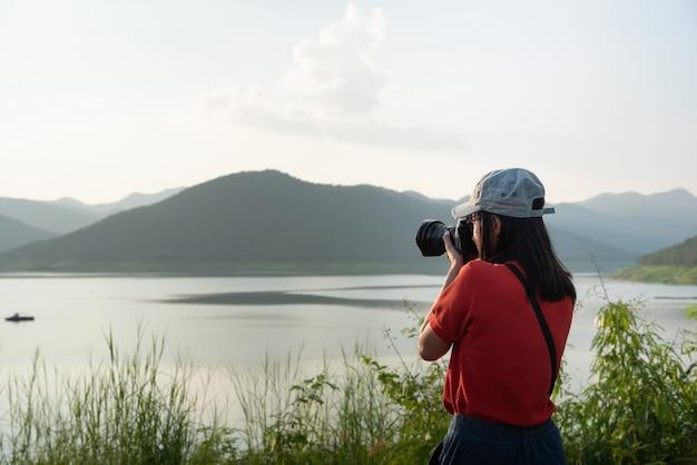 Les femmes utilisent l'appareil photo pour prendre des photos du tourisme de nature. Photo Premium