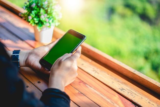 Les femmes utilisent un téléphone intelligent et tactile pour la communication et la vérification sur écran vert Photo Premium