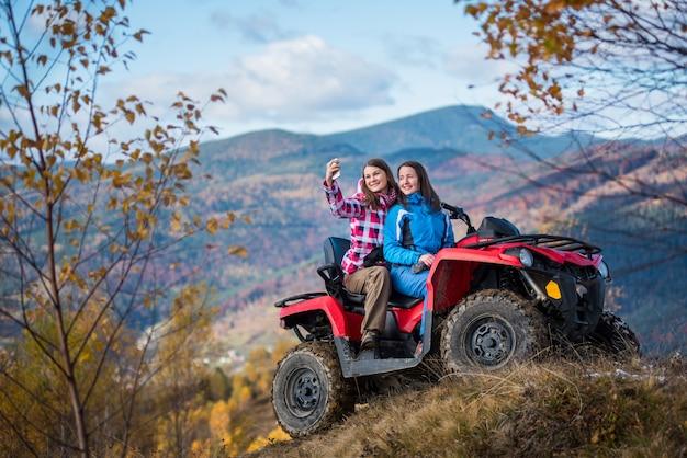 Femmes en vestes sur un vtt rouge à la colline fait selfie au téléphone Photo Premium