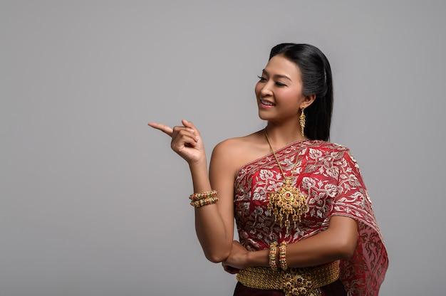 Des femmes vêtues de costumes thaïlandais symboliques pointant du doigt Photo gratuit