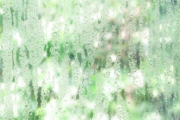 Fenêtre en verre transparent avec des gouttes d'eau, nature verte pour le fond Photo Premium