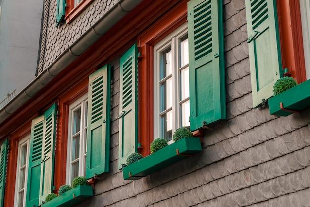 Fenêtres Européennes Avec Des Volets En Bois Verts Dans La Vieille Maison. Extérieur Photo Premium