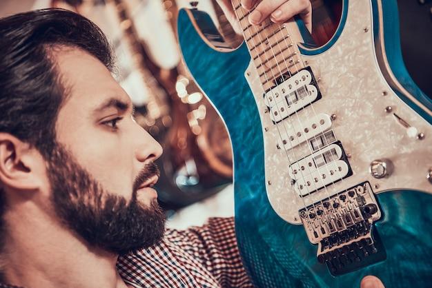 Fermer. adulte homme barbu examine de près la guitare électrique Photo Premium