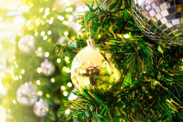 Fermer. un cadeau en or est accroché à l'arbre de noël. arrière-plan flou Photo Premium