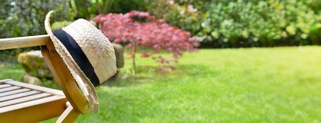 Fermer sur un chapeau de paille sur l'accoudoir d'une chaise dans un jardin en été Photo Premium