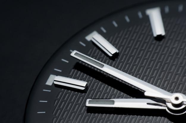 Fermer dans le sens des aiguilles d'une montre sur l'arrière-plan du cadran noir montre-bracelet dans un style rétro Photo Premium