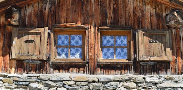 Fermer Sur Deux Petites Fenêtres Sur Une Façade De Chalet De Montagne Photo Premium