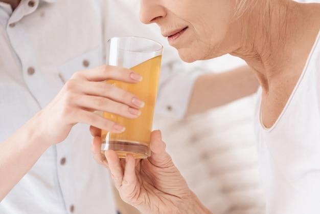 Fermer. femme âgée buvant du jus à l'hôpital. Photo Premium