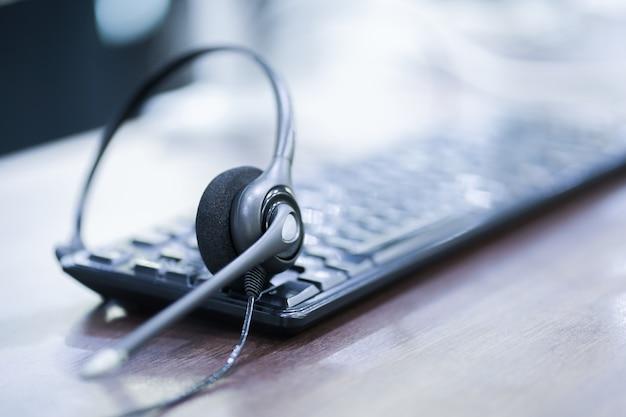 Fermer le focus sur le dispositif de casque du centre d'appels au bureau de l'ordinateur clavier Photo Premium