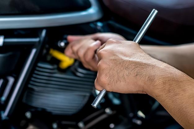 Fermer. les gens qui se tiennent la main réparent une moto utilisez une clé et un tournevis Photo Premium
