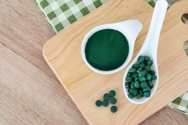 Fermer une poudre de spiruline dans un bol et des pilules de spiruline, un régime alimentaire sain et un concept de nutrition détox Photo Premium