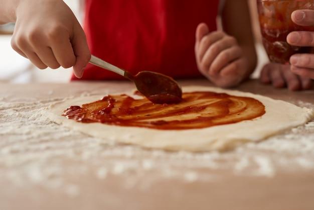 Fermer. Préparation De Pizza Avec Une Sauce Tomate. Photo Premium